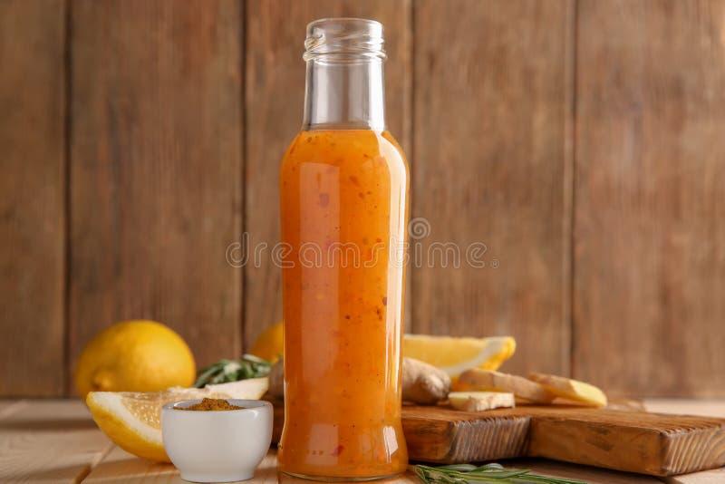 Bouteille avec de la sauce, le gingembre et les citrons savoureux sur la table en bois images stock
