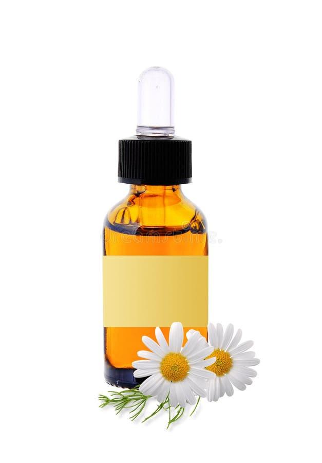 Bouteille avec des fleurs d'huile et de camomille d'essence images libres de droits
