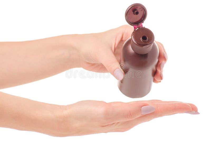 Bouteille avec des mains de femelle de lotion d'huile de cosmétiques image stock