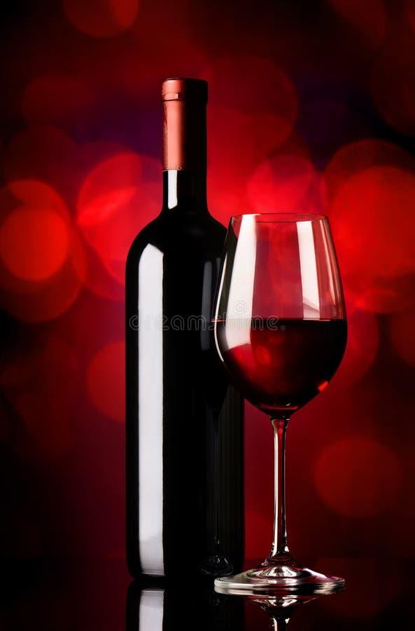 Bouteille avec du vin sur le rouge photographie stock libre de droits