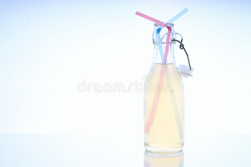 Bouteille avec la boisson froide sur la table en verre avec deux pailles photographie stock
