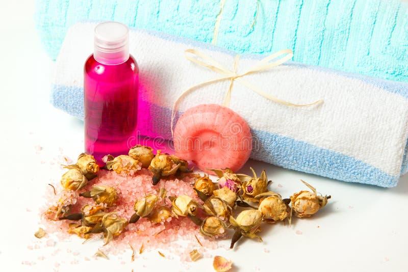 Bouteille avec le gel rose, le savon fait main, le sel et les bourgeons roses photographie stock
