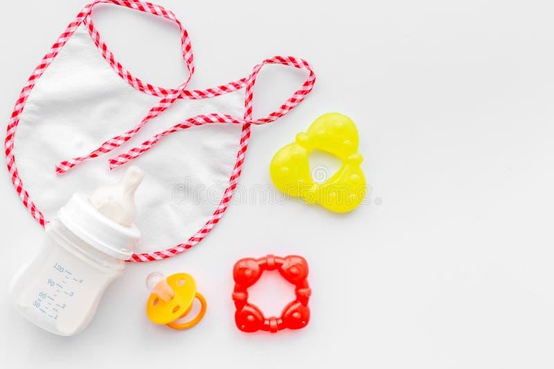 Bouteille avec le lait maternel et la nourriture, les jouets et le bavoir sains en poudre par formule de nourrisson sur la moquer images libres de droits
