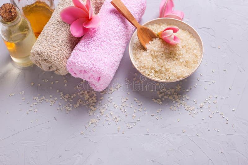 Bouteille avec le pétrole d'arome, le sel de mer dans la cuvette, la serviette et les fleurs sur le GR photos stock