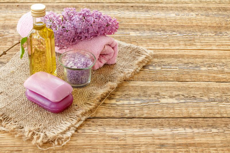 Bouteille avec le p?trole, la cuvette avec du sel de mer, le savon et la serviette avec les fleurs lilas sur le fond en bois photos libres de droits