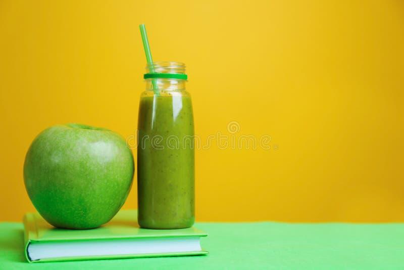 Bouteille avec le smoothie sain frais, la pomme verte et le livre sur la table image libre de droits