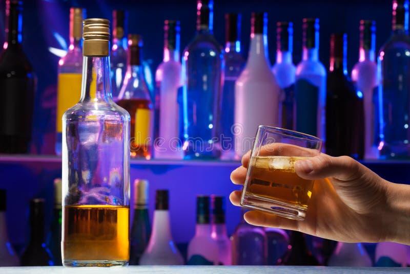 Bouteille avec le whiskey et le verre dans la main de l'homme photo stock