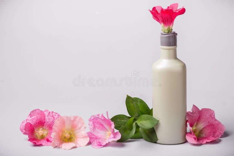 Bouteille avec les fleurs cosmétiques de produit et de mauve image libre de droits