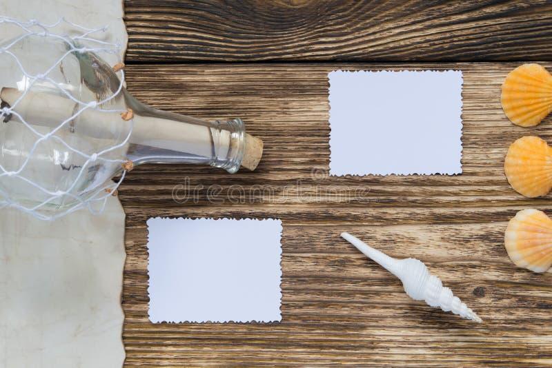 bouteille avec un message sur la table et deux photos en blanc images stock