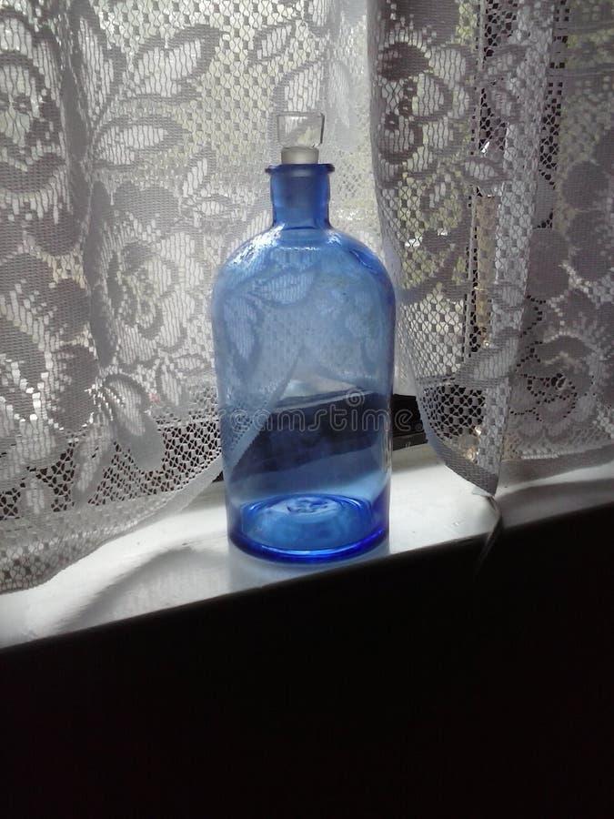 Bouteille bleue dans la fenêtre de dentelle photos libres de droits