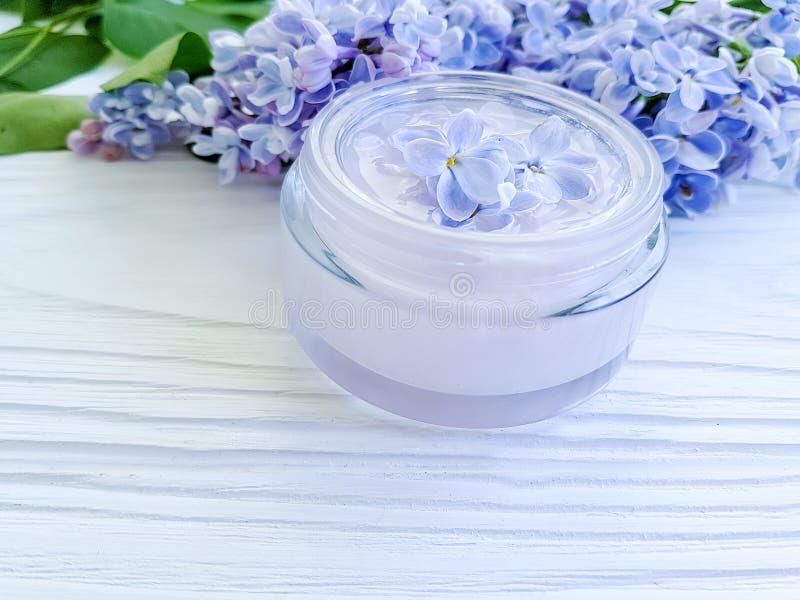 Bouteille crème cosmétique organique, thérapie lilas de fleur de relaxation d'extrait sur le fond en bois blanc images stock