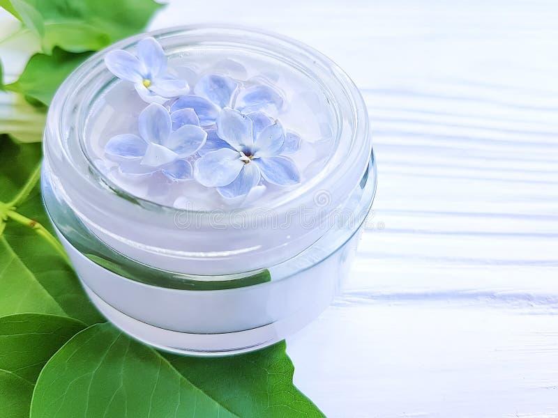 Bouteille crème cosmétique, thérapie lilas de fleur de relaxation d'extrait sur le fond en bois blanc image stock