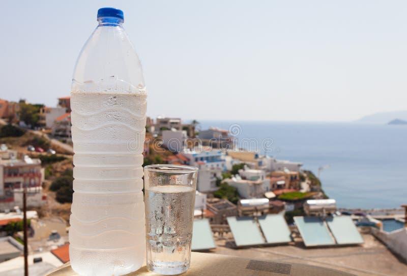 Bouteille d'eau complètement de l'eau avec des baisses et de verre sur le fond de ville et de mer Méditerranée et le soleil images stock