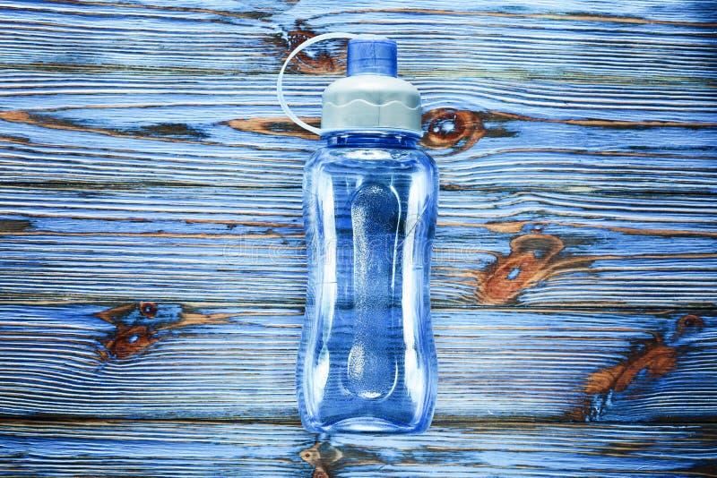 Bouteille d'eau en plastique de forme physique sur le panneau en bois de vintage bleu images libres de droits