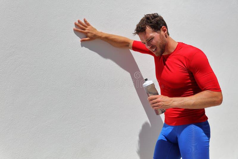 Bouteille d'eau potable déshydratée épuisée fatiguée de coureur d'homme après séance d'entraînement Personne courante faisant une photographie stock