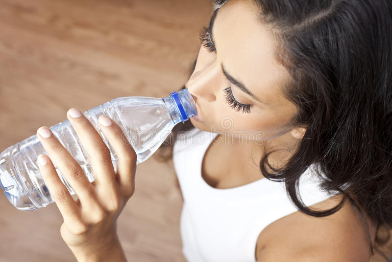 Bouteille d'eau potable de fille hispanique de femme de Latina image stock
