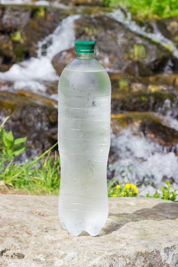 Bouteille d'eau potable froide contre du plan rapproché de courant de montagne images stock