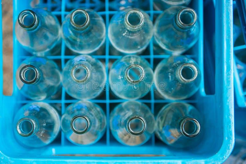 Bouteille d'eau vide dans des caisses en plastique bleues photos stock
