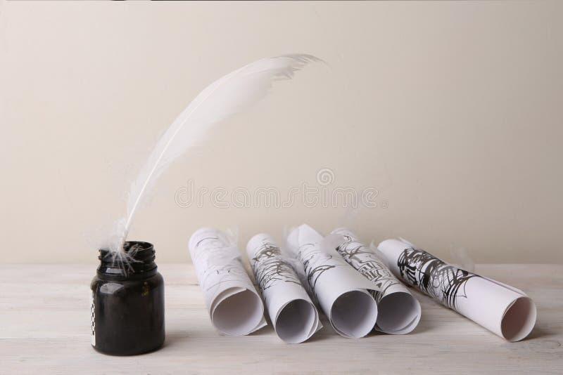 Bouteille d'encre avec des rouleaux de plume et de papier avec le dessin d'encre images libres de droits