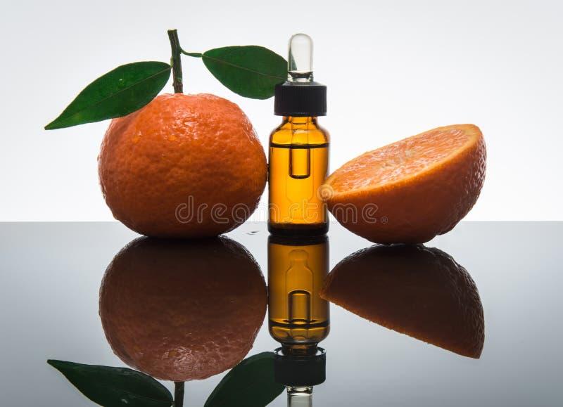 Bouteille d'huile essentielle de mandarine/mandarine avec le compte-gouttes photographie stock libre de droits