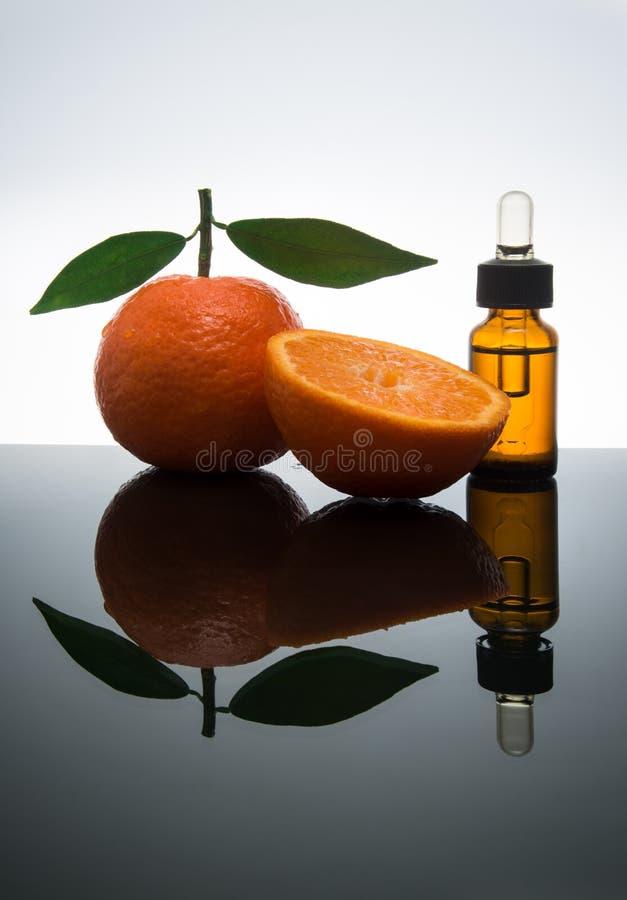 Bouteille d'huile essentielle de mandarine/mandarine avec le compte-gouttes photos stock