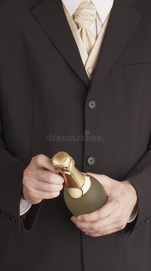 Bouteille d'une manière élégante rectifiée de Champagne d'ouverture d'homme image stock