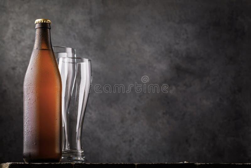Bouteille de bière blonde et de deux verres vides sur une table en bois comme besoin humain photo libre de droits