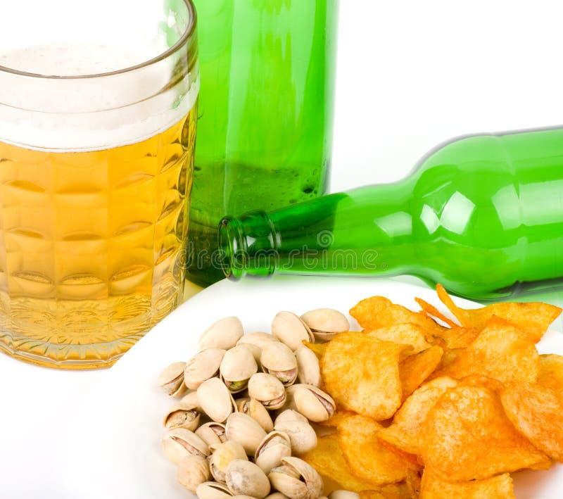 Bouteille de bière et pommes chips vertes, pistaches photo libre de droits
