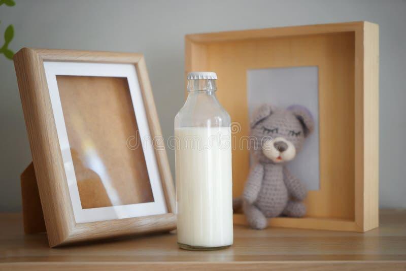 Bouteille de cadres de lait et de photo sur la table en bois à l'intérieur images stock