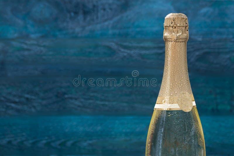 Bouteille de Champagne avec des gouttes de l'eau contre un Ba de couleur essence photos stock