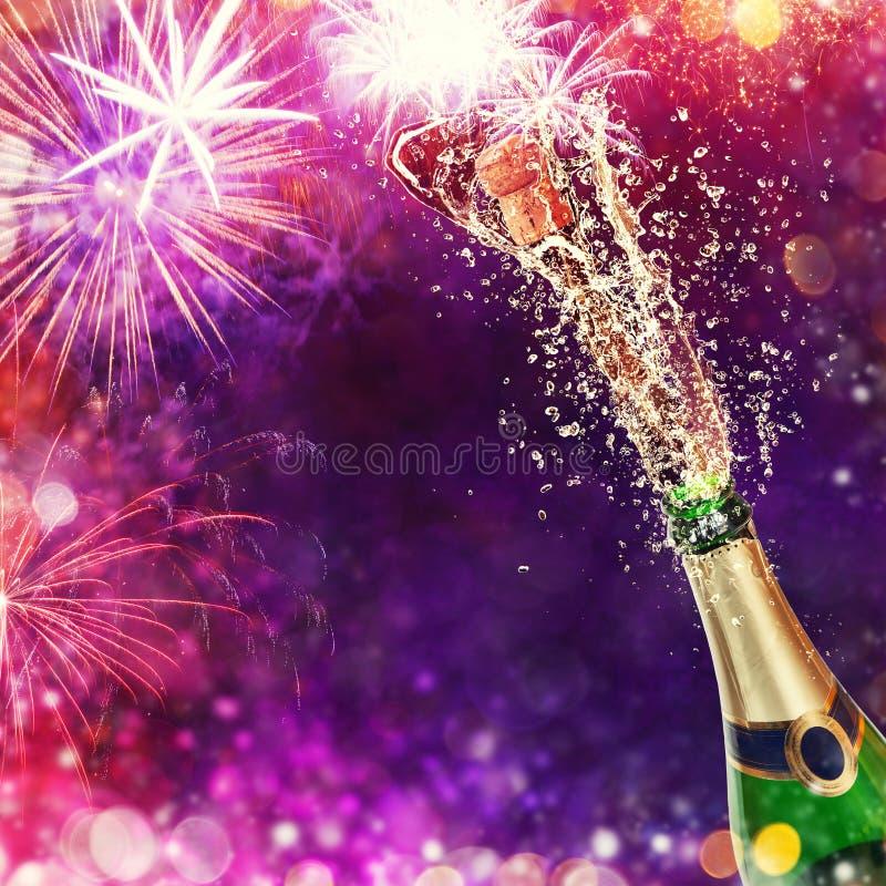 Bouteille de champagne avec des verres au-dessus de fond de feux d'artifice images stock