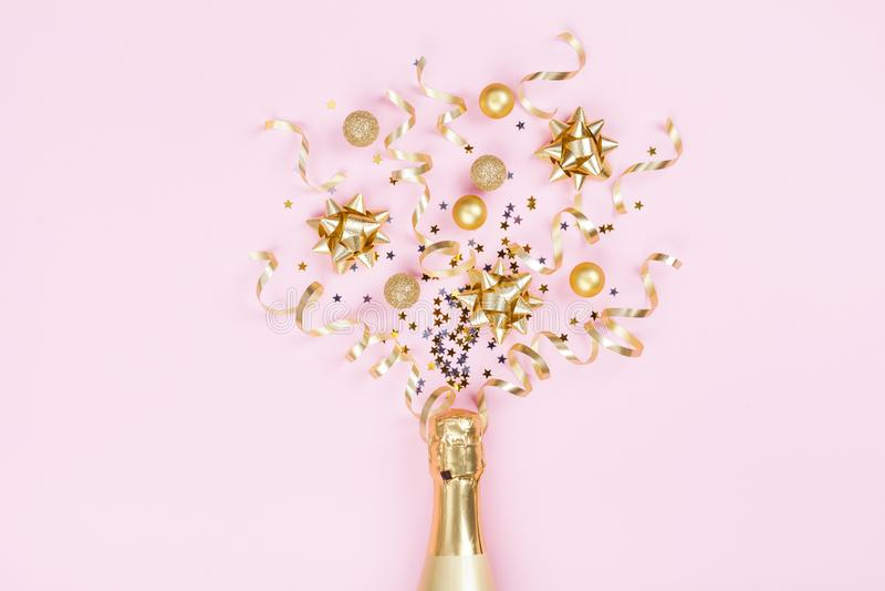 Bouteille de Champagne avec la décoration de Noël des étoiles de confettis, des boules d'or et des flammes de partie sur le fond  photos stock