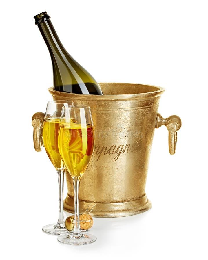 Bouteille de Champagne dans le seau à glace d'or avec des verres de plan rapproché de champagne sur un fond blanc Toujours durée  photographie stock