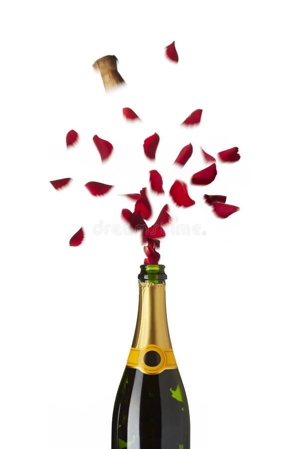 Bouteille de champagne sautant les pétales de rose rouges avec du liège dans l'a image libre de droits