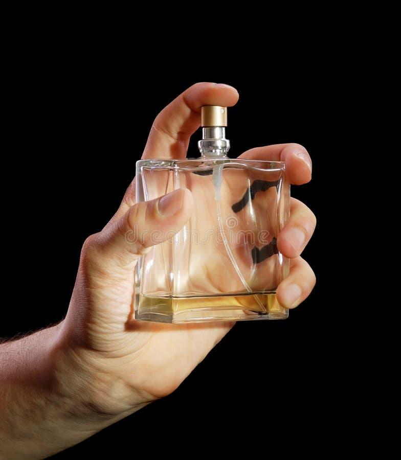 Bouteille de cologne dans une main à l'homme photos stock