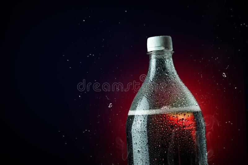 Bouteille de kola avec l'éclaboussure de glace sur le fond foncé Bouteille de boisson non alcoolisée dans le concept de partie de images libres de droits