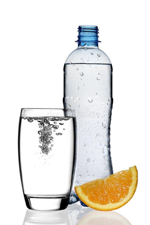 Bouteille de l'eau avec la part et la glace oranges images stock