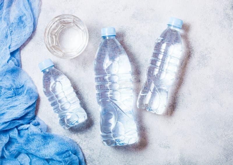 Bouteille de l'eau minérale de scintillement avec le verre de la glace et du tissu bleu sur le blanc photographie stock