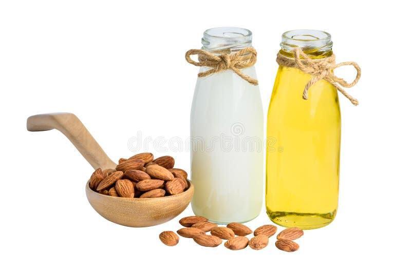 Bouteille de lait et de pétrole d'amande avec les amandes épluchées dans le spoo en bois photos stock