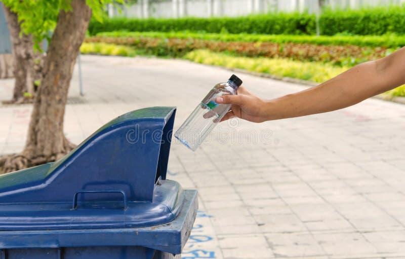 Bouteille de lancement de main dans des poubelles photo libre de droits