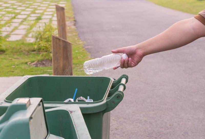 Bouteille de lancement de main dans des poubelles image libre de droits