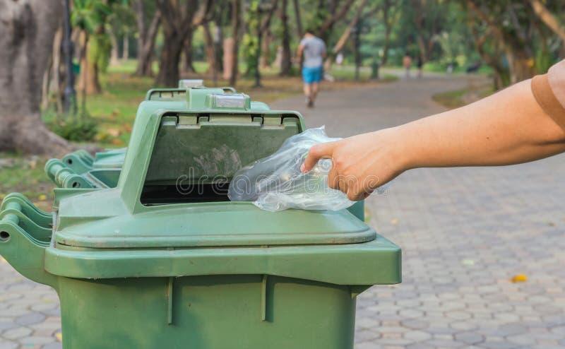 Bouteille de lancement de main dans des poubelles photographie stock