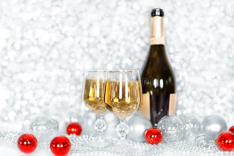 Bouteille de No?l ou de nouvelle ann?e de champagne, deux pleins verres de champagne sur les boules de table, brillantes et de sc photos libres de droits