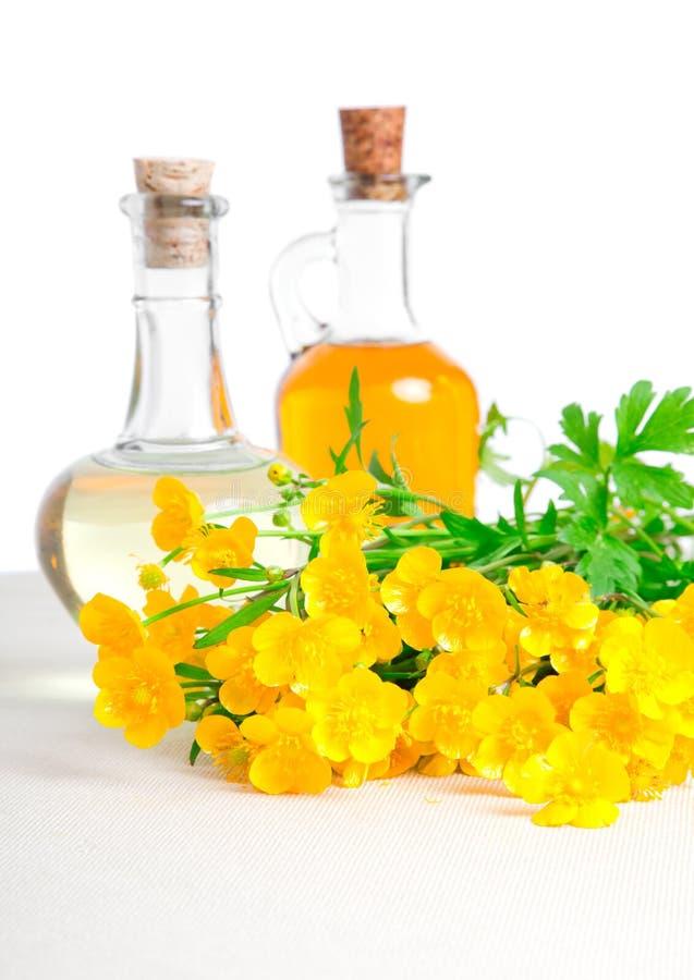 Bouteille de pétrole avec la fleur de graine de colza photos stock
