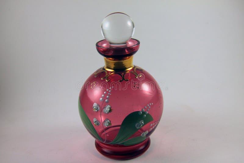 Bouteille de parfum en verre peinte à la main rouge photographie stock