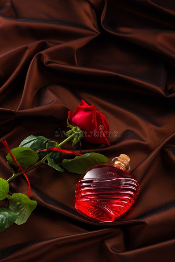 Bouteille de parfum et de roses sur le satin rouge photographie stock libre de droits