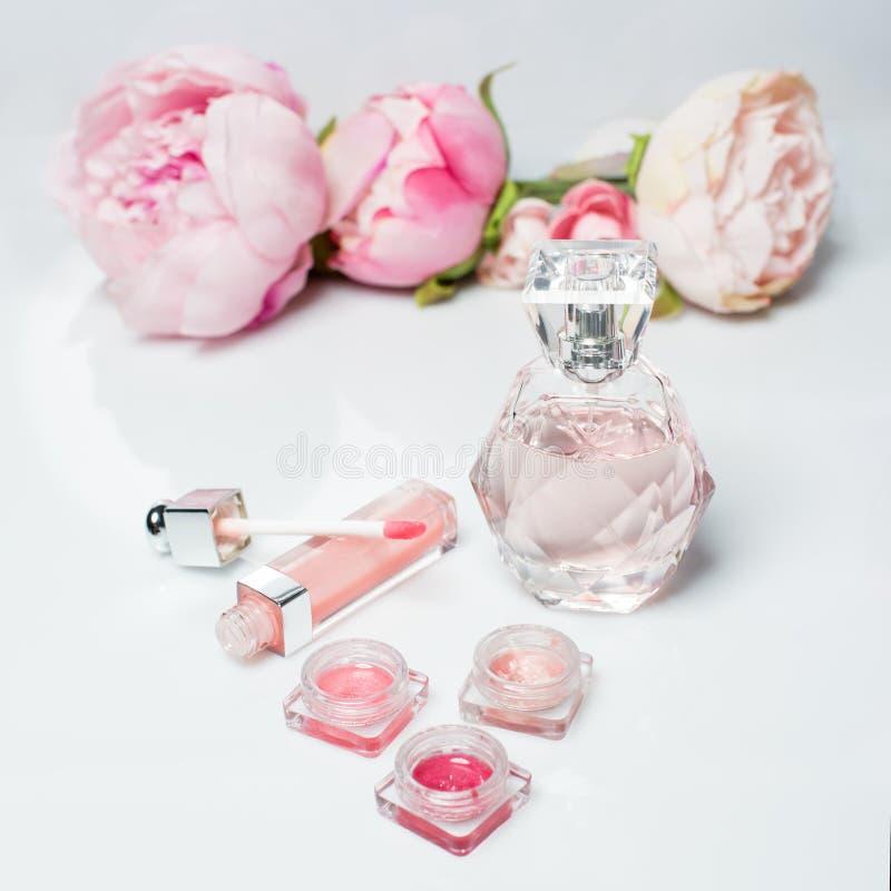 Bouteille de parfum, vernis à ongles, rouge à lèvres De mode de femme toujours la vie Sautez les choses femelles avec des fleurs  photos libres de droits