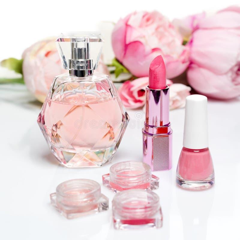 Bouteille de parfum, vernis à ongles, rouge à lèvres De mode de femme toujours la vie Sautez les choses femelles avec des fleurs  image libre de droits