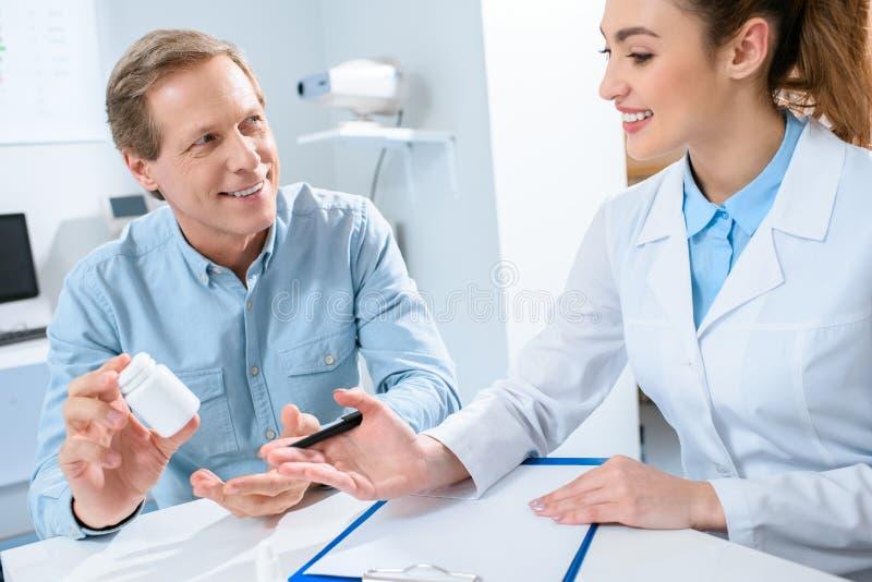bouteille de participation d'homme de pilules et consultation de avoir avec le beau docteur image stock