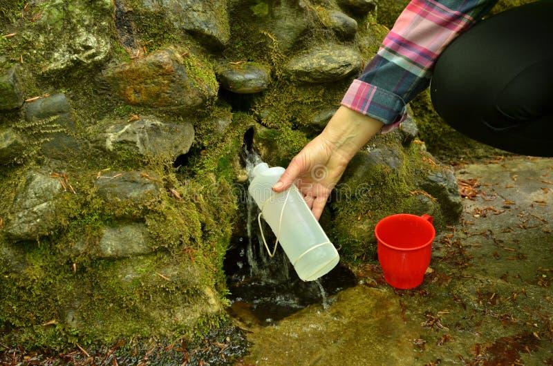Bouteille de participation de main de femme avec l'eau de source photographie stock